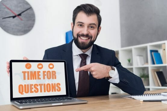 cheerful businessman pointing at laptop with time for questions inscription at workplace in office