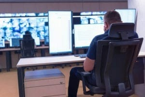 Security guard monitoring modern CCTV cameras in their business