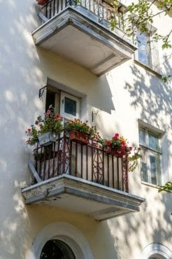 View Of A Small Balcony With Flowers In Pots On The Facade Of A Multistory Building