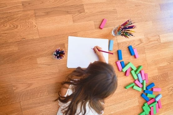 Adorable toddler lying down on the floor drawing using paper and pencils at kindergarten