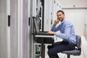 man looking up from working with servers