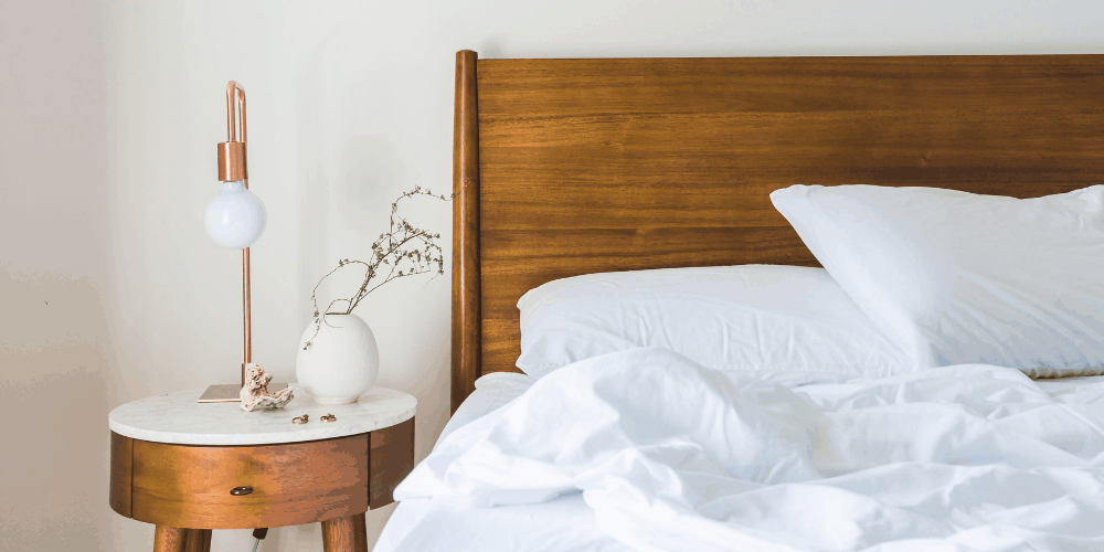 a nightstand and bed with white bedsheets and pilows