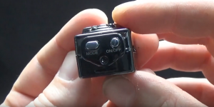 a man holding a mini camera showing the on and off button